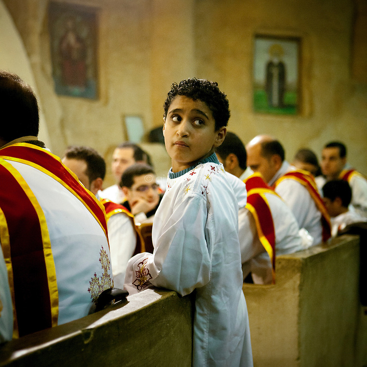 Egypt / Cairo / 6.1.2013 / Altar boy during the Coptic Christmas celebrations at a cave chapel. The chapel is part of the Simon the Tanner Monastery, hidden in a cave in the Mokattam hills, above Cairo's Manshiyet Nasser (also known as Garbage City, Zabbaleen's settlement). © Giulia Marchi