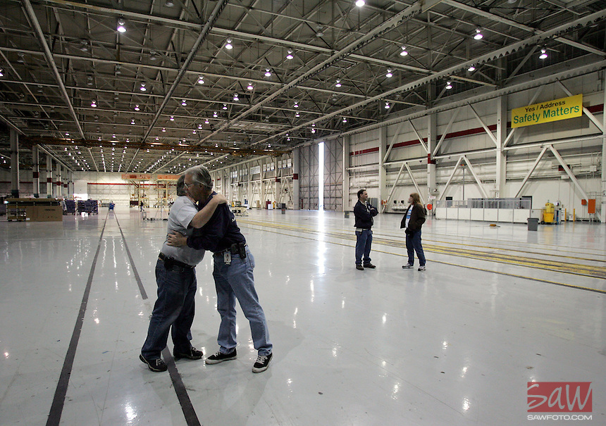 A goodbye hug inside the closing Boeing hanger for Harold Mutz,left, and Greg Testh, right. The Boeing engineers have worked together for 26 years. Boeing employees delivered the last commercial passenger jet to the built in California, Thursday, April 20, 2006, in Long Beach, Calif.