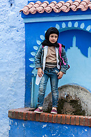 Chefchaouen, Morocco.  Young Pre-teen Berber Girl Combining Western-style Levis with Conservative Muslim Headscarf.