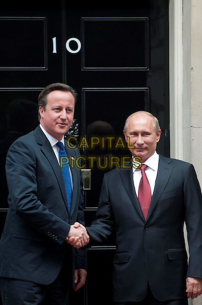 David Cameron & Vladimir Putin.Russian president, Vladimir Putin, at No.10 Downing Street to hold talks with Prime Minister David Cameron, London, England..August 2nd, 2012.politics PM half length black suit blue tie door  red shaking hands.CAP/BF.©Bob Fidgeon/Capital Pictures.