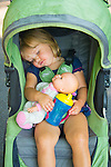 Toddler with doll baby sleeping in walker push buggy.