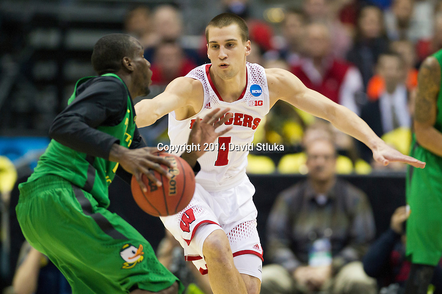 Wisconsin Badgers guard Ben Brust (1) plays defense against Oregon Ducks guard Jason Calliste (12) during the third-round game in the NCAA college basketball tournament Saturday, April 22, 2014 in Milwaukee. The Badgers won 85-77. (Photo by David Stluka)