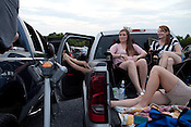 Molly Frazier, right, and her sister Paige Frazier of New Market, Virginia, talk with friends before the movies start at Family Drive-In Theatre in Stephens City, Virginia on July 20, 2013. CREDIT: Lance Rosenfield/Prime