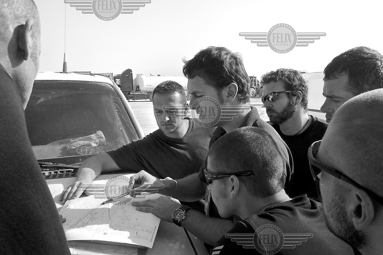 Team leader Kent Paget uses a pen on a map as he briefs other private security operators from the British company ArmorGroup before a reconnaissance mission on the notoriously dangerous road from Al Asad air base to the military outpost Camp Wolf in north western Iraq on October 23 2006. The coalition forces and civilian administration in Iraq depend heavily on the controversial presence of thousands of private security personnel in their reconstruction efforts and military operations.