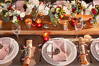 Christmas crackers, pine cones and glimmering tealights create a festive feel to a dining table set with simple white china on a rustic linen cloth