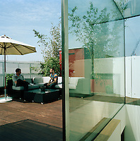 The roof terrace offers a green oasis in the heart of a city. Seating and a low table are arranged on the iroko decking.