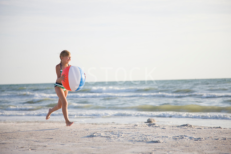 USA, Florida, St. Pete Beach, girl (8-9) running with ball on beach