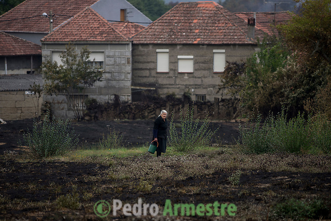 A resident of the hamlet of Vilela, stands in a burnt field a day after a wildfire in Cualedro, near Ourense on August 31, 2015. A fire broke out on August 30, 2015 around noon in the Cualedro town in Galicia, northwest Spain, affecting at least 3,180 hectares of forest, as seven fires continued to burn in Spain, three in Galicia, one in Cantabria, one in Castile and Leon, one in Catalonia and Extremadura. © Pedro ARMESTRE
