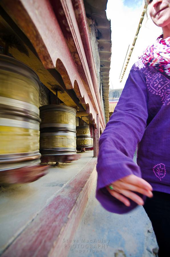 Western traveler spinning prayer wheels, Shey Palace, Naropa Royal Palace, Shey, Ladakh, India.