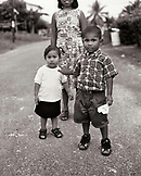 PANAMA, Bocas del Toro, portrait of a boy with his sister, mother and paper airplane in the streets of Bocas, Central America (B&W)