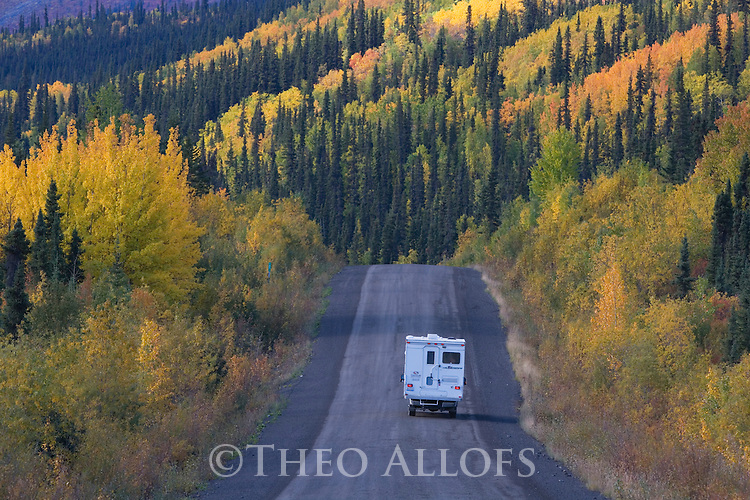 Dempster Highway winding through mountains and forests in fall colors, northern Yukon, Canada