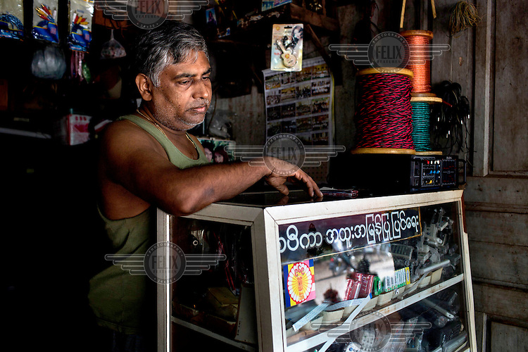 A Hindu shopkeeper displays a sticker for the Buddhist nationalist 969 movement on his counter in Mawlamyine, Mon State. /Felix Features