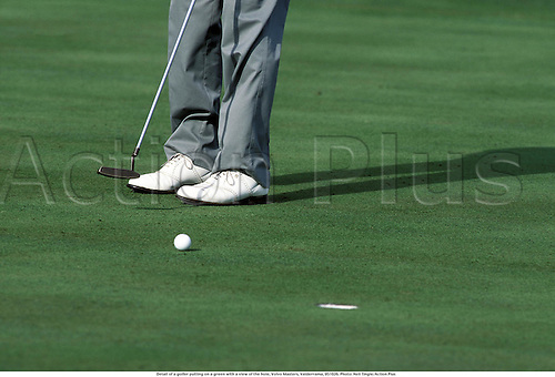 Detail of a golfer putting on a green with a view of the hole, Volvo Masters, Valderrama, 951026. Photo: Neil Tingle/Action Plus...1995.club.putt putter.  detail.sports equipment. s.  ident.golfers golf.closeup close up close-up.illustration.leg legs.foot feet
