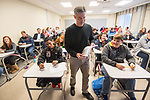 John Latartara, associate professor of music, hands out the final in his music theory class.  Photo by Kevin Bain/University Communications Photography