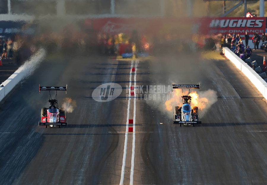Feb 23, 2019; Chandler, AZ, USA; NHRA top fuel driver Antron Brown (right) explodes an engine alongside Doug Kalitta during qualifying for the Arizona Nationals at Wild Horse Pass Motorsports Park. Mandatory Credit: Mark J. Rebilas-USA TODAY Sports