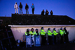 Activists protesting againts Dale Farm Traveller eviction from the roof while riot police officers watched. They were arrested they day after after especial unit police unlocked them. October 2011, Basildon UK