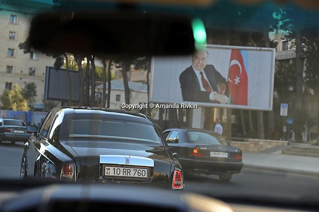 Ibrahim Ibrahimov rides in his black Rolls Royce passed a ubiquitous billboard of former Azerbaijani President Heydar Aliyev, a fellow Nakhchivani, as seen through the windshield of his chase car in Baku, Azerbaijan on August 16, 2012.