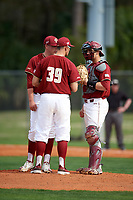 Boston College Eagles pitching coach Alex Trezza (39) talks with starting pitcher Jacob Stevens (44) and catcher Gian Martellini (2) during a game against the Minnesota Golden Gophers on February 23, 2018 at North Charlotte Regional Park in Port Charlotte, Florida.  Minnesota defeated Boston College 14-1.  (Mike Janes/Four Seam Images)