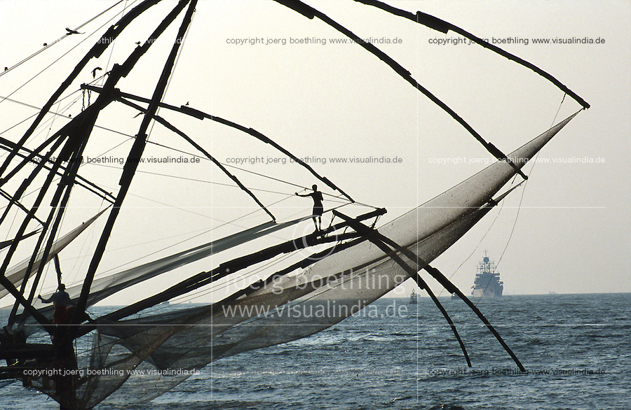 INDIA Kerala, Fort Cochin, chinese fishing net at port entry, indian navy ship / INDIEN Kerala, Cochin Kochi, lokale Küstenfischer leeren die chinesischen stationären Senknetze an Hafeneinfahrt , indisches Marine Schiff