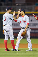 Mookie Betts (12) of the Pawtucket Red Sox high fives teammate Garin Cecchini (3) following their win over the Charlotte Knights at BB&T Ballpark on August 9, 2014 in Charlotte, North Carolina.  The Red Sox defeated the Knights  5-2.  (Brian Westerholt/Four Seam Images)