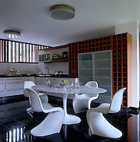 The sleek kitchen-diner has a black granite tiled floor, marble-topped Saarinen table and white Verner Panton chairs
