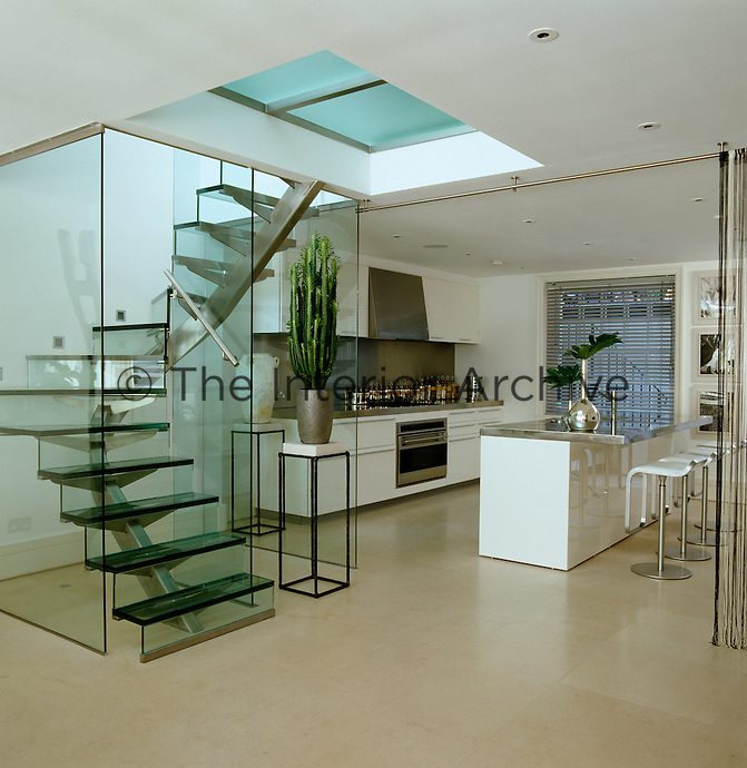 A glass and steel staircase that leads from the ground floor into the basement kitchen creates an impression of openness