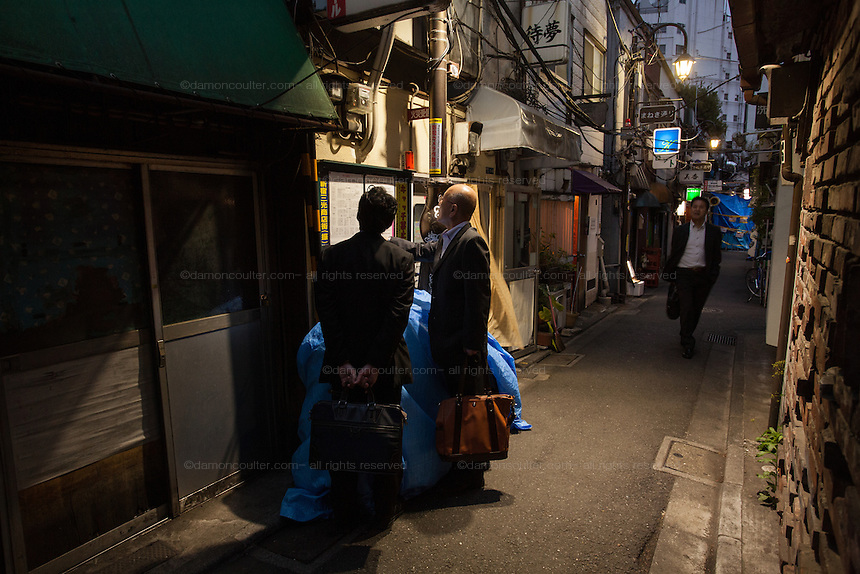 Salarymen check a map to locate a bar in the night life district of Golden Gai in Shinjuku, Tokyo, Japan. Friday April 22nd 2016