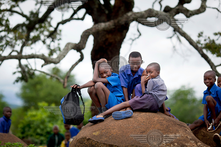 Pupils at Zvehuru primary school sitting on rocks near the school's borehole.