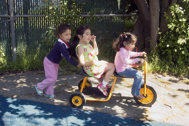 Berkeley CA  Girls in joyful play on preschool playground in bilingual, Spanish-English program