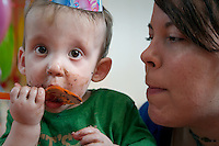 Mother looking at her son celebrating first birthday with covered with cake and holding a plastic spoon and wearing a birthday hat