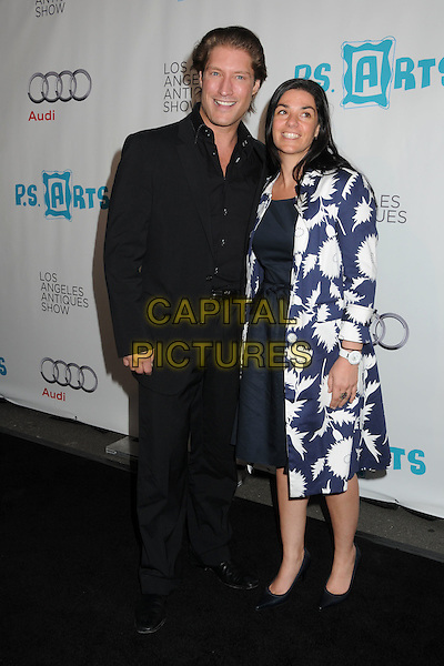 SEAN KANAN & GUEST.16th Annual Los Angeles Antiques Show Opening Night Gala Benefiting P.S. Arts held at Barker Hangar, Santa Monica, California, USA..April 13th, 2011.full length black suit white blue print jacket dress.CAP/ADM/BP.©Byron Purvis/AdMedia/Capital Pictures.