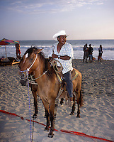 A man who rents horses searches for potential clients on playa Zicatela. Puerto Escondido during spring break (semana santa) vacation 2006