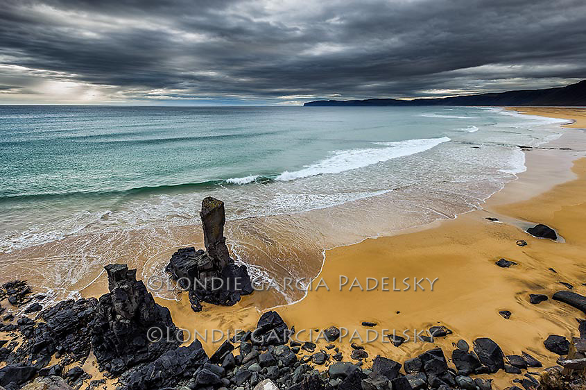 Storm clouds over a lone seastack and a long stretch of beach in Iceland