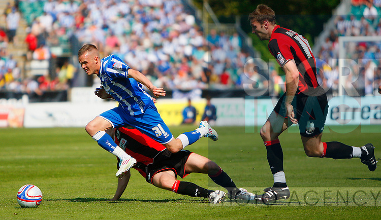 Craig Noone of Brighton & Hove Albion is tackled by Scott Arfield of Huddersfield Town during the English League One football match between Brighton & Hove Albion and Huddersfield Town at Withdean Stadium, Brighton, England, on April 30, 2011. Photo Credit SPORTIMAGE/JAKE BADGER