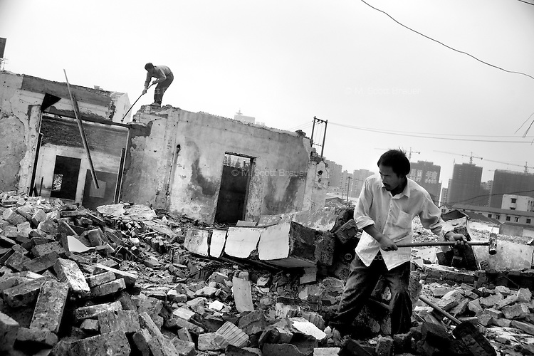 Workers break away bricks and concrete to find rebar and other metals for salvage in Nanjing, Jiangsu, China.