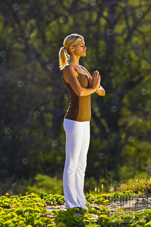 A young woman performs yoga at Makena, Maui.