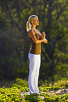 A young woman performs yoga at Makena, Maui.