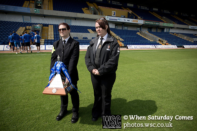 Mansfield Town Football Club Open Day, 14/07/2013. Field Mill stadium, League Two. Two security guards holding the Conference National trophy at Field Mill stadium during an open day held for Mansfield Town supporters. Mansfield Town achieved promotion back to England's Football League by winning the Conference National in season 2012-13. Field Mill was the oldest ground in the Football League, hosting football since 1861 although some reports date it back as far as 1850, with Mansfield Town having played there since 1919. Photo by Colin McPherson.