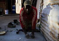 Ein illegaler Goldgräber (Name unbekannt), zermalmt im südafrikanischen Slum New Canada, Johannesburg, Steine. Das ist nötig, um später mit Chemikalien die Goldpartikel zu isolieren.