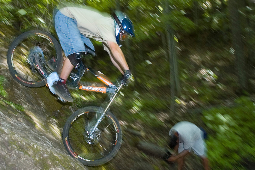 Mountain bikers drop down the face of a cliff while freeriding near Marquette Michigan.