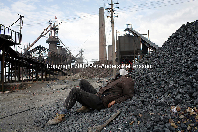 TURPAN, CHINA - JUNE 9: A worker rests on a pile of coal early in the morning in a steel factory on June 9, 2007, about 10 kilometers outside Turpan, China. The factory is privately owned and about one hundred men work there. It was built only four years ago and the working conditions are difficult and unhealthy. (Photo by Per-Anders Pettersson).....