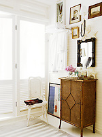 A guest bathroom is furnished with a wicker chair and cabinet