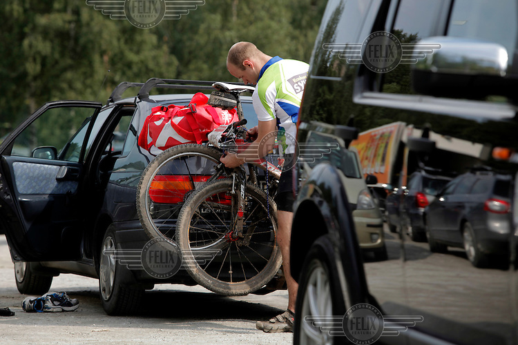 A rider fixes bicycles to the back of his car after the race. Grenserittet is a 80km mountain bike race starting in the Swedish town of Strömstad, ending up in the Norwegian town Halden. The interest for these kind of bike races has exploded in Norway the last few years, particularly with middle age affluent men.
