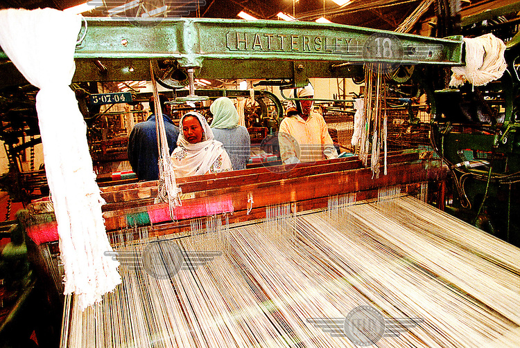 Eritrea, Asmara, 25.12.2000.Workers operating a huge weaving machine in the Asmara Textile Factory..©Stefan Boness/Panos Pictures