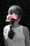 Young girl, seen waist up from back, with pink bow in hair braid, highlighted by sun. Girl, wearing tank top dress, against dark background. Selective coloring; everything but bow black and white.