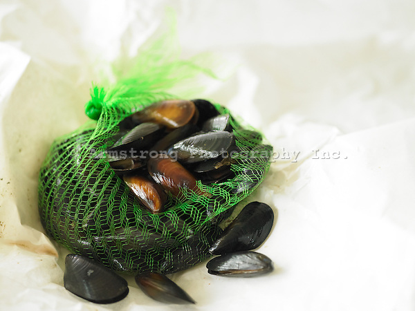 A bag of fresh live mussels on butcher paper