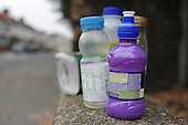 An assortment of plastic bottles on a wall on a London street.