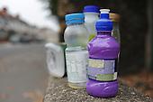 An assortment of plastic bottles on a wall on a London street.