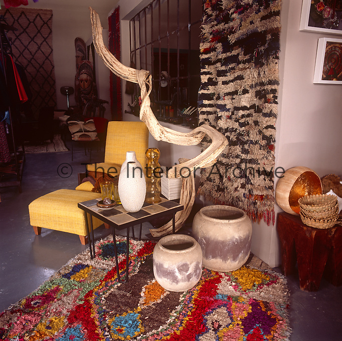 Ceramic pots and glassware stands on a retro table next to a yellow upholstered chair and footstool. Rustic pots are set on a patterned rag rug.