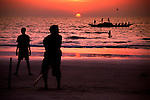 Young boys play beach cricket  as a fishing boat sets out to sea in Goa, India..